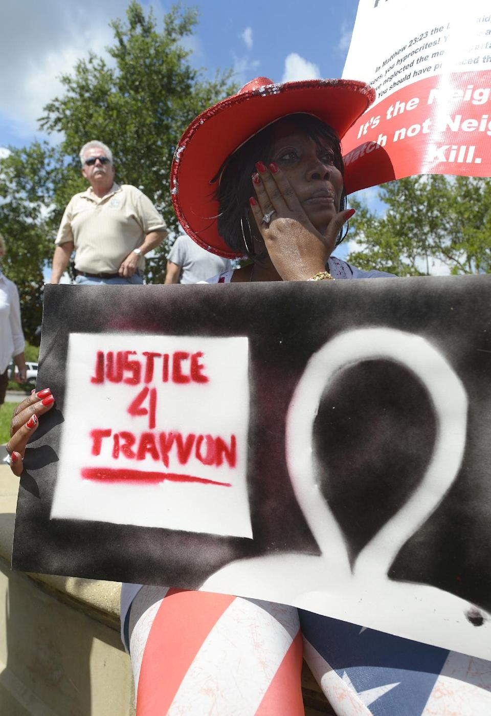 Cynthia Bradford, of Casselberry, Fla., wipes away tears while showing her support for Trayvon Martin outside the Seminole County Courthouse in Sanford, Fla., Saturday, July 13, 2013. Zimmerman has been charged in the 2012 shooting death of Trayvon Martin.(AP Photo/Phelan M. Ebenhack)