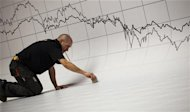 Worker puts finishing touches to a stage under a graph at the Madrid stock exchange