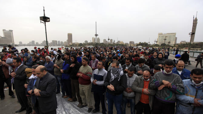 Egyptian protesters perform prayers on Qasr Al-Nile bridge leading to Tahrir Square, Cairo, Egypt, Monday, Jan. 28, 2013. Health and security officials say a protester has been killed in clashes between rock-throwing demonstrators and police near Tahrir Square in central Cairo. The officials say the protester died Monday on the way to the hospital after being shot. (AP Photo/Khalil Hamra)