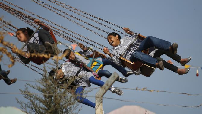 Palestinian girls ride a swing in an amusement park built on the land of a former Israeli settlement in the central Gaza Strip