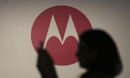 A woman takes a picture in front of a Motorola logo before the worldwide presentation of the Moto G mobile phone in Sao Paulo