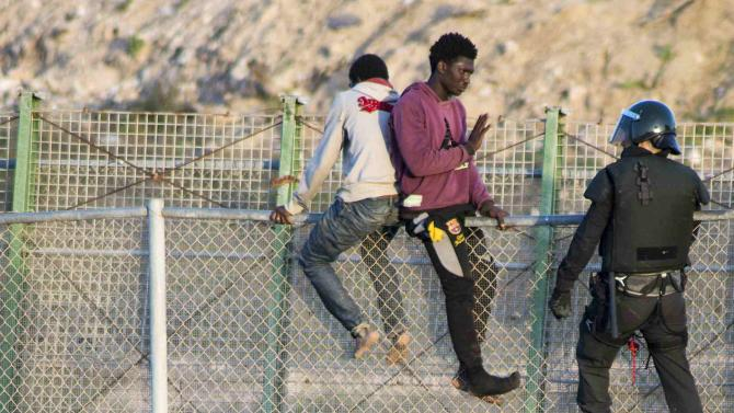 African migrants are taken down from a border fence between Morocco and Melilla