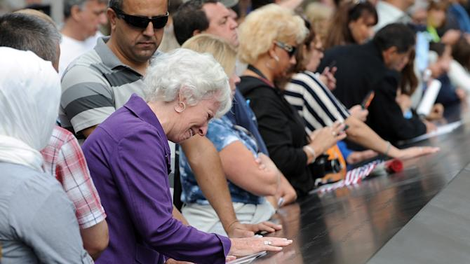 A woman cries over a name inscribed on the edge of the north pool at the National September 11 Memorial in New York during the ceremony marking the 10th anniversary of the attacks on the World Trade Center, Sunday, Sept. 11, 2011. (AP Photo/Justin Lane, Pool)