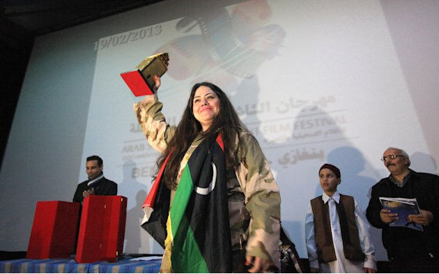 "Director Neveen Shalaby holds her Best Documentary Film award for her film ""The Agenda and Me"" at the Arab Screen Independent Film Festival in Benghazi"