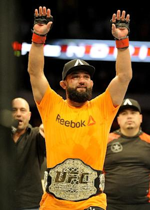 Johny Hendricks celebrates after beating Robbie Lawler during a UFC 171 mixed martial arts welterweight title bout, Saturday, March 15, 2014, in Dallas. Hendricks won by decision. (AP Photo/Matt Strasen)
