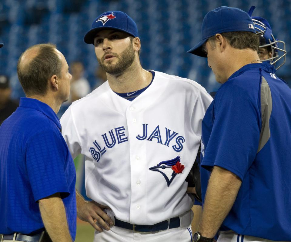 Toronto Blue Jays starting pitcher Brandon Morrow, center, talks with manager John Farrell, right, and a trainer before being pulled in the first inning of an interleague baseball game against the Washington Nationals in Toronto on Monday, June 11, 2012. (AP Photo/The Canadian Press, Frank Gunn)