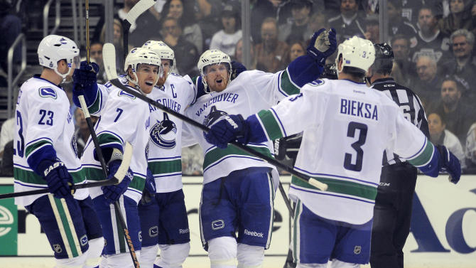 Vancouver Canucks defenseman Kevin Bieksa, right, celebrates his goal against the Los Angeles Kings with teammates, from left, defenseman Alexander Edler, of Sweden; left wing David Booth; center Henrik Sedin, of Sweden; and left wing Daniel Sedin, of Sweden, during the second period of Game 4 in a first-round NHL Stanley Cup playoff series, Wednesday, April 18, 2012, in Los Angeles. (AP Photo/Mark J. Terrill)