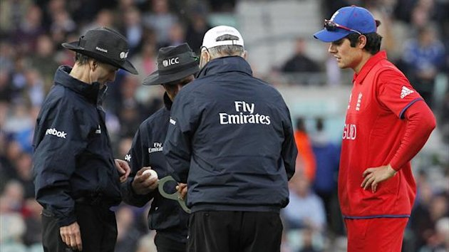 England's captain Alastair Cook (R) looks on as the umpires decide whether to change the ball during a 2013 ICC Champions Trophy cricket match between England and Sri Lanka at The Oval cricket ground in London, on June 13, 2013 (AFP)