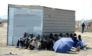 Striking Lonmin platinum mine workers sit in the shade in Marikana, listening to their union representatives reporting back from a meeting with the management. Worker turnout at the mine on Friday plunged to 0.31 percent, a record low since workers walked off the job on August 10