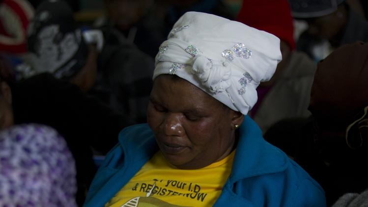A woman prays after a technical glitch prevented a screening of the memorial service of former South African President Nelson Mandela at the Nelson Mandela Museum in Qunu