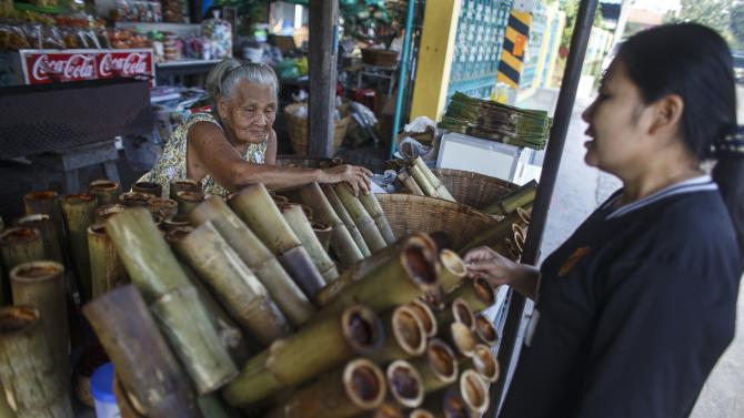 A woman buys Khao Lam, a sticky rice dish baked inside a bamboo cylinder, at a shop in Chonburi