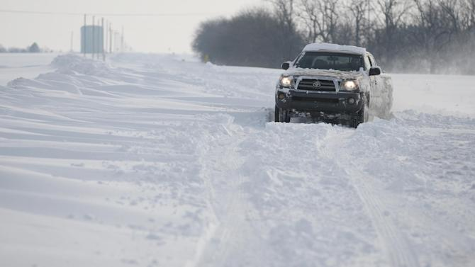 A truck makes it's way up the snow covered road in Sedgwick County, Kan. , Tuesday, Feb. 26, 2013. The second major snowstorm in a week battered the nation's midsection Tuesday, dropping a half-foot or more of snow across Missouri and Kansas and cutting power to thousands.  Gusting winds blew drifts more than 2 feet high and created treacherous driving conditions for those who dared the morning commute.  (AP Photo/The Wichita Eagle, Bo Rader)