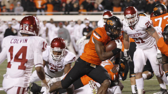 Oklahoma State running back Joseph Randle, center, scores past Oklahoma defenders defensive back Aaron Colvin (14), linebacker Corey Nelson (7) and linebacker Tom Wort (21) in the second quarter of an NCAA college football game in Stillwater, Okla., Saturday, Dec. 3, 2011. (AP Photo/Sue Ogrocki)