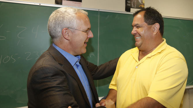 Aaron Cosar, right, greets former Oklahoma Gov. Brad Henry, left, at The Education and Employment Ministry (TEEM), where Cosar works as a life-skills instructor, in Oklahoma City, Monday, June 24, 2013. Henry, who commuted Cosar's life sentence and signed his parole after Cosar served nearly 25 years in prison for the shooting death of an Ada, Okla. man after a night of drinking when Cosar was 19 years old, surprised the ex-convict by dropping by the classroom where Cosar now teaches life skills to other former inmates. (AP Photo/Sue Ogrocki)