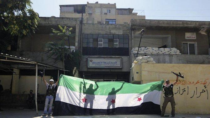 This citizen journalism image taken on Friday, Aug. 3, 2012 purports to show Syrian rebels celebrating after taking over the Ansari police station in the northern city of Aleppo, Syria on August 3, 2012. (AP Photo) THE ASSOCIATED PRESS IS UNABLE TO INDEPENDENTLY VERIFY THE AUTHENTICITY, CONTENT, LOCATION OR DATE OF THIS CITIZEN JOURNALIST IMAGE