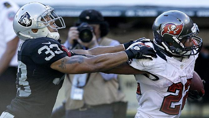 Tampa Bay Buccaneers running back Doug Martin (22) stiff arms Oakland Raiders defensive back Tyvon Branch (33) as he runs for a 45-yard touchdown during the third quarter of an NFL football game in Oakland, Calif., Sunday, Nov. 4, 2012. Martin, a rookie who was born in Oakland, rushed for a franchise-record 251 yards and four touchdowns. (AP Photo/Ben Margot)