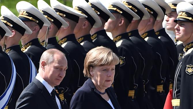 Russian President Vladimir Putin (L) and German Chancellor Angela Merkel attend a wreath-laying ceremony at the Tomb of the Unknown Soldier by the Kremlin Wall in Moscow on May 10, 2015