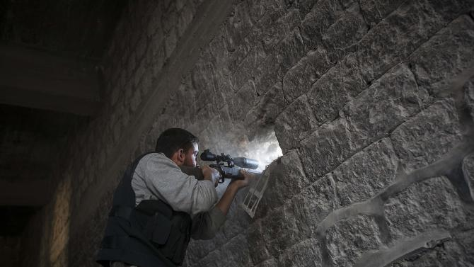 In this Sunday, Nov. 04, 2012 photo, a rebel sniper aims through a hole in the wall that overlooks a position held by Syrian troops loyal to President Bashar Assad hidden in a nearby building as they attempt to gain ground on the rebel lines during heavy clashes in the Jedida district of Aleppo, Syria. The uprising against Assad started with peaceful demonstrations in March last year, but has since morphed into a bloody civil war. Activists say more than 36,000 people have been killed in 19 months of fighting. (AP Photo/Narciso Contreras)