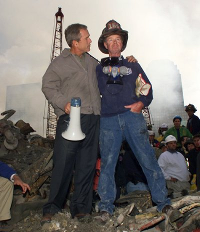 President George W. Bush embraces firefighter Bob Beckwith while standing in front of the collapsed World Trade Center buildings in New York on Septem...