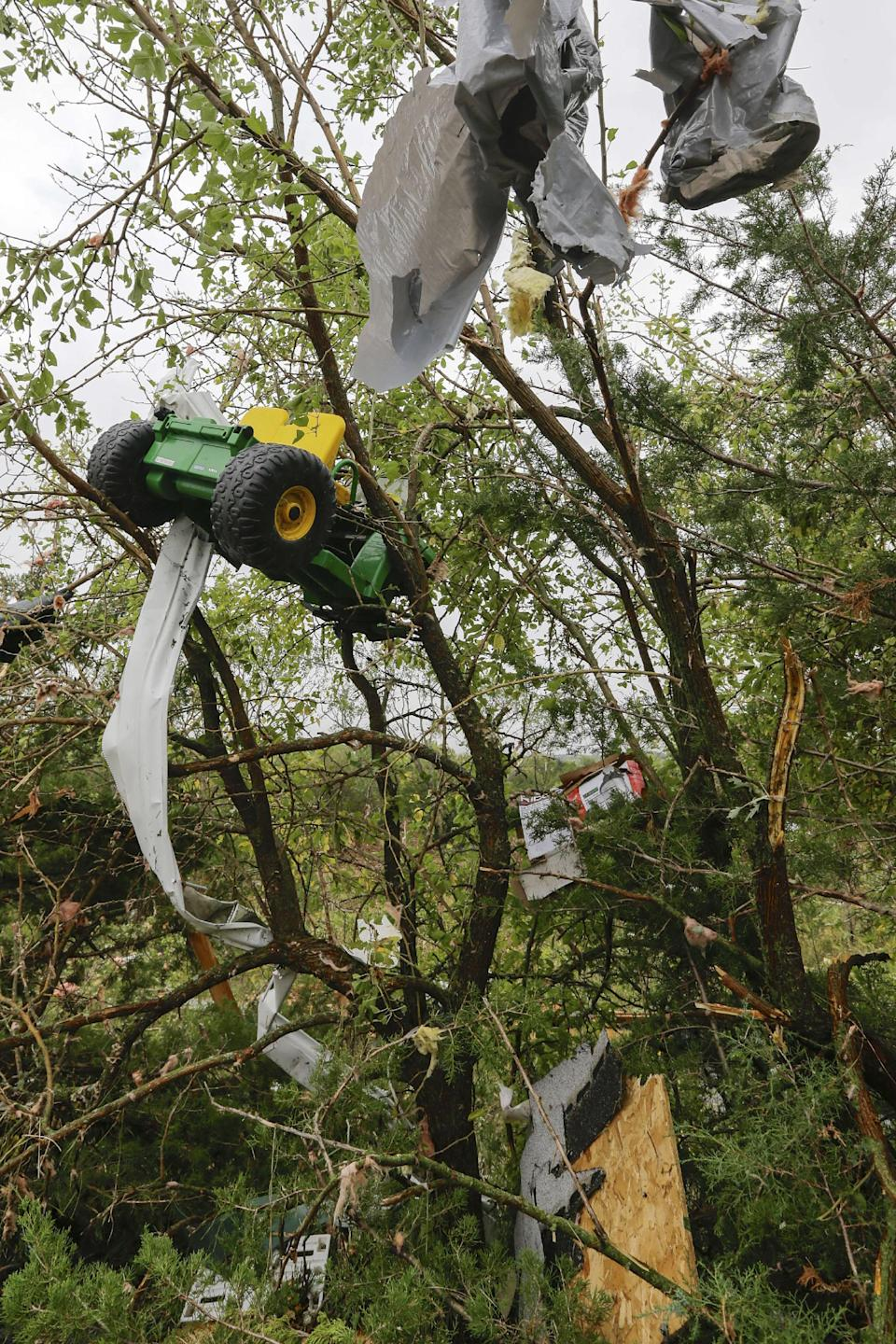 Debris, including a toy tractor, are trapped in a tree following a tornado in Hickman, Neb., Friday, Oct. 4, 2013. Powerful storms crawled into the Midwest on Friday, dumping heavy snow in South Dakota, spawning a tornado in Nebraska and threatening dangerous thunderstorms from Oklahoma to Wisconsin. (AP Photo/Nati Harnik)
