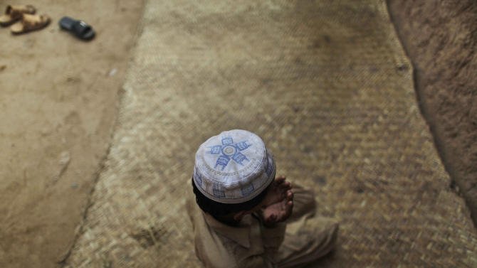 A Pakistani boy prays before attending a daily class to learn how to read verses of the Quran, at a mosque in a poor neighborhood of Rawalpindi, Pakistan, Tuesday, Oct. 19, 2010. (AP Photo/Muhammed Muheisen)