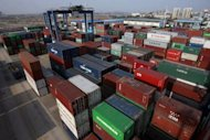 Shipping containers pile up at a container port in Wuhan, in central China&#39;s Hubei province. China swung back to a trade surplus last month, reversing a massive deficit recorded in February, the official Xinhua news agency said Tuesday