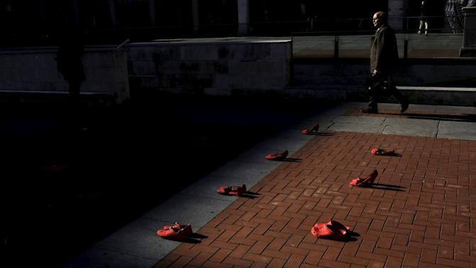 Man walks past red shoes placed at Plaza Mayor, as part of an installation to protest against gender violence and femicide, in Valladolid