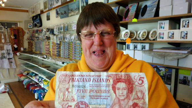FILE - In this March 4, 2012 file photo, Sybie Summers, owner of the Pod gift shop, holds up a five pounds local banknote with an illustration of the British monarch Queen Elizabeth, in Stanley, Falkland Islands. The government of the Falkland Islands says that the disputed south Atlantic territory will hold a referendum on whether to remain a British territory. (AP Photo/Michael Warren, File)