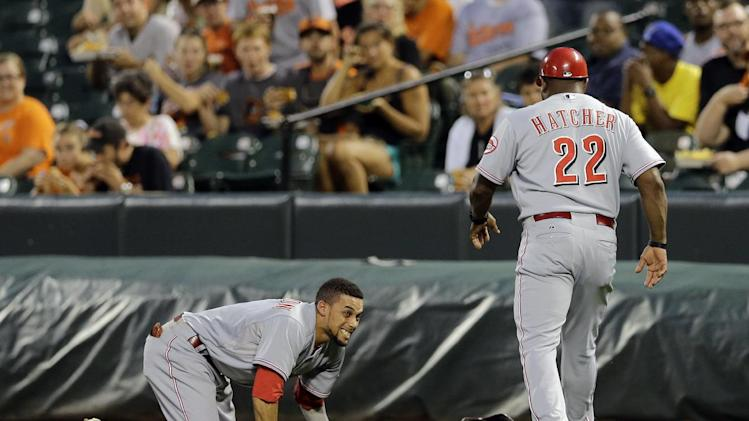 Cincinnati Reds first base coach Billy Hatcher, right, checks on Cincinnati Reds' Billy Hamilton after Hamilton collided with umpire Mike DiMuro at first base in the first inning of an interleague baseball game against the Baltimore Orioles, Tuesday, Sept. 2, 2014, in Baltimore. (AP Photo/Patrick Semansky)