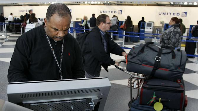 David Caradine works at upgrading the software at a United Airlines e-ticket kiosk at Chicago's O'Hare International Airport Thursday, Nov. 15, 2012. Passengers in several cities say a massive computer outage has stranded United passengers at airports across the country, resulting in at least the third major computer outage for the Chicago-based airline since June. (AP Photo/Charles Rex Arbogast)