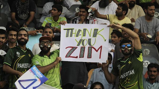 Pakistan's cricket fans hold up a poster to welcome the Zimbabwe cricket team at the Gaddafi stadium in Lahore, Pakistan, Friday, May 22, 2015. The game marks a return of international cricket to Pakistan for the first time since gunmen attacked buses carrying the Sri Lankan cricket team and match officials in this eastern city six years ago. (AP Photo/K.M. Chaudary)