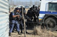 Police officers close to protesting miners near a platinum mine in Marikana on August 16. South Africa opened an inquiry on Monday into the police killing of at least 34 miners during the day of violence in August, hoping to find out how a dispute over pay ended in a bloodbath