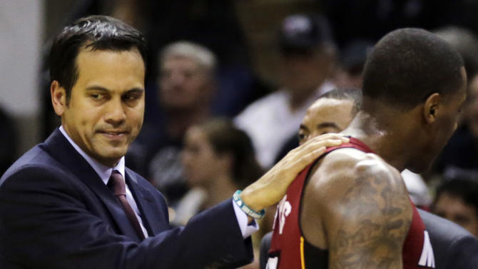 Miami Heat head coach Erik Spoelstra, left, gives guard Mario Chalmers a pat on the sideline against the San Antonio Spurs during the second half in Game 1 of the NBA basketball finals on Thursday, June 5, 2014 in San Antonio. (AP Photo/Eric Gay)
