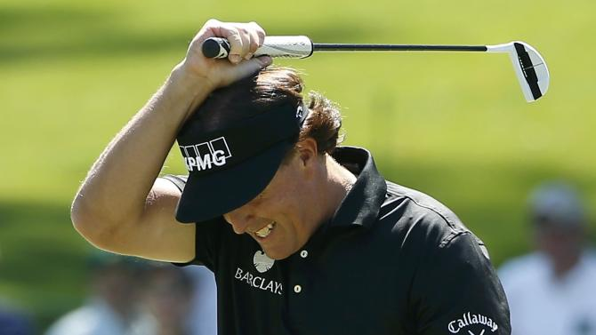 U.S. golfer Phil Mickelson reacts after missing a putt on the sixth hole during the first round of the 2014 Masters golf tournament at the Augusta National Golf Club in Augusta