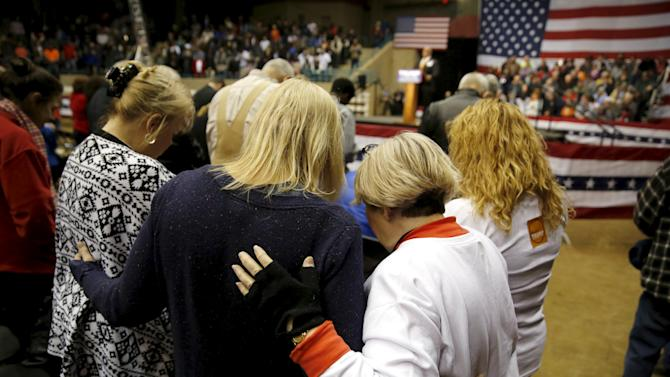 Supporters of Trump hold each other during a prayer before a rally with Trump at Clemson University's livestock arena in Pendleton