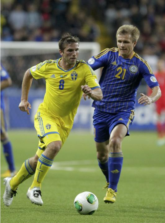 Kazakhstan's Valeri Korobkin fights for the ball with Sweden's Anders Svensson during their 2014 World Cup qualifying soccer match at the Astana Arena stadium in Astana