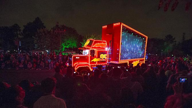 "People watch the character of Mack Truck from the movie ""Cars"" featured in ""Paint the Night - All-New Electrical Parade"" during Disneyland Diamond Celebration in Anaheim"