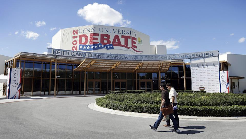 Workers walk outside the Keith C. and Elaine Johnson Wold Performing Arts Center, site of Monday's presidential debate between President Barack Obama and Republican presidential candidate, former Massachusetts Gov. Mitt Romney, Sunday, Oct. 21, 2012, in Boca Raton, Fla. (AP Photo/Charlie Neibergall)