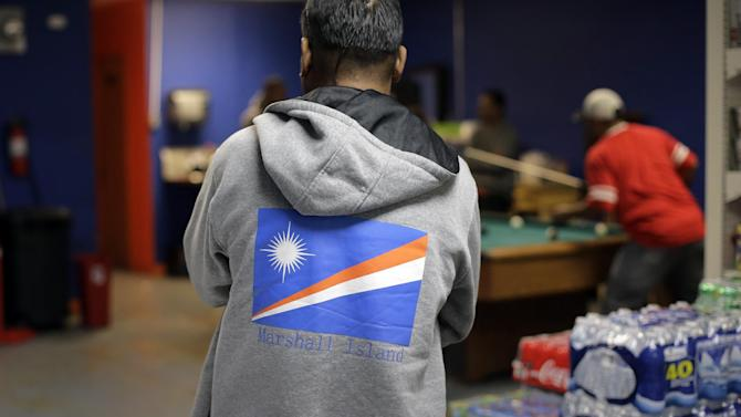 """Marshallese men congregate in a back room of the Jakejeboleo market, a gathering place for Marshallese, Thursday, Nov. 19, 2015, in Springdale, Arkansas. Marshallese have settled in Hawaii, Oklahoma and the Pacific Northwest, Springdale has taken on a special significance. Their numbers there have grown in the thousands. Some jokingly call it """"Springdale Atoll,"""" and there's even a Marshallese consulate, the only one on the mainland U.S. (AP Photo/Eric Gay)"""