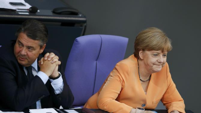 German Chancellor Merkel and Economy Minister Gabriel listen during a parliamentary debate on the Greek debt crisis at the German lower house of parliament Bundestag in Berlin