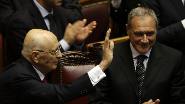 Italian President Giorgio Napolitano, flanked by the chairman of the Senate Pietro Grasso, right, salutes lawmakers after delivering his speech at the lower chamber in Rome, Monday, April 22, 2013. President Giorgio Napolitano headed Monday into his unprecedented second term with the daunting task of trying to find a candidate who can form a government two months after national elections left Italy with no clear winner and an increasingly discredited political class. (AP Photo/Gregorio Borgia)