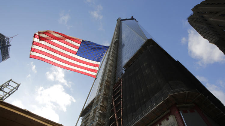 An American flag flies next to One World Trade Center, Tuesday, Dec. 11, 2012 in New York.  A 408-foot spire is expected to rise on top of the tower into the Manhattan sky by spring. (AP Photo/Mark Lennihan)