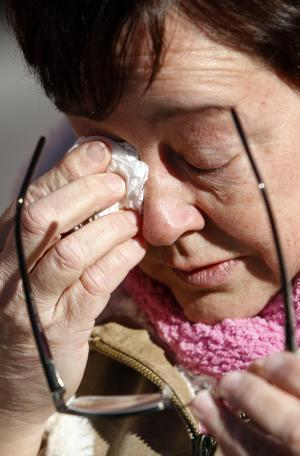 Christine Piacentini wipes her eyes near a makeshift memorial, not pictured, for her daughter, homicide victim Nicole Piacentini, in the Kensington neighborhood of Philadelphia, Tuesday, Dec. 21, 2010.  Police in Philadelphia are pleading with residents not to become vigilantes as the search continues for a man accused in two stranglings and several other attacks. (AP Photo/Matt Rourke)