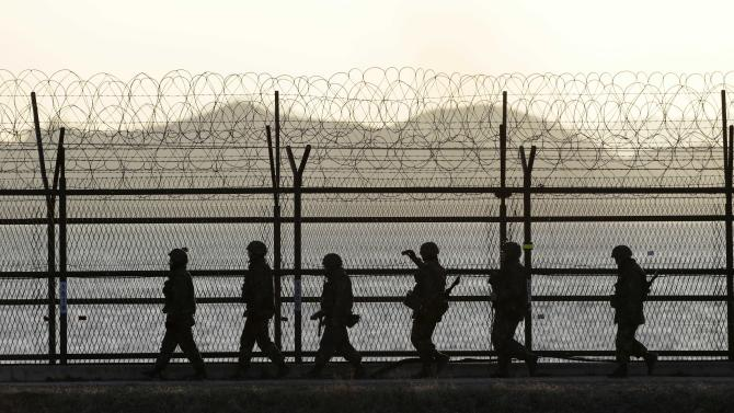 South Korean army soldiers patrol along a barbed-wire fence at sunset near the border village of Panmunjom, which has separated the two Koreas since the Korean War, in Paju, north of Seoul, South Korea, Sunday, April 7, 2013. A top South Korean national security official said Sunday that North Korea may be setting the stage for a missile test or another provocative act with its warning that it soon will be unable to guarantee diplomats' safety in Pyongyang. But he added that the North's clearest objective is to extract concessions from Washington and Seoul. (AP Photo/Lee Jin-man)