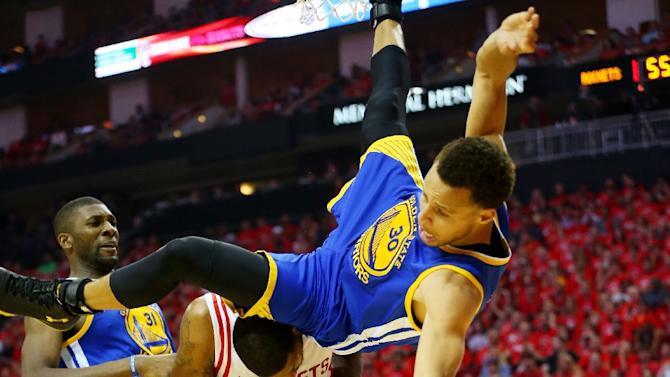 Golden State Warriors' Stephen Curry falls over Houston Rockets' Trevor Ariza during Game Four of the Western Conference Finals at Toyota Center on May 25, 2015