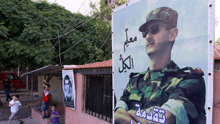 "In this Tuesday, April 30, 2013 photo, Lebanese boys play under a large poster, right, of Syrian President Bashar Assad with Arabic writing that reads, ""everybody's teacher,"" in the predominantly Alawite neighborhood of Jabal Mohsen in the northern port city of Tripoli, Lebanon.  Lebanese members of the Syrian leader's Alawite sect fear their tiny community will be a casualty of the civil war raging in the neighboring country. Already, Sunni extremists have stoned a school bus, vandalized stores and beaten or stabbed a number of men in a wave of attacks against Lebanese Alawites, raising fears of more violence should Assad be removed from power.(AP Photo/Bilal Hussein)"