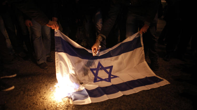 Protesters burn an Israeli flag during a protest against Israel's bombardment of the Gaza Strip, in front of the Israeli embassy in Athens Saturday, Nov. 17, 2012. Several thousand marchers are commemorating the 39th anniversary of a deadly student uprising against the then ruling dictatorship, with more than 6,000 police deployed in the center of the Greek capital. Protesters after marching to the U.S embassy  continued to demontsrate outside the Israeli embassy against bombardment of the Gaza Strip.  (AP Photo/Kostas Tsironis)