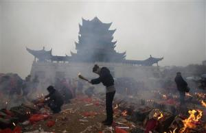 File photo of worshippers burning incense to pray for wealth on the fifth day of Chinese Lunar New Year at Guiyuan Buddhist Temple in Wuhan