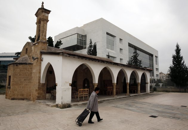 A woman pulls a cart in front of Ayia Paraskevi Orthodox church as the Central Bank of Cyprus is seen in the background in Nicosia