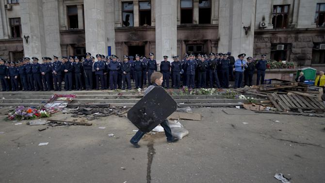 A child walks carrying a shield back dropped by police troops guarding the burnt trade union building in Odessa, Ukraine, Saturday, May 3, 2014, where more than 30 people died trying to escape during clashes the day before. Odessa had been largely tranquil since the February toppling of President Viktor Yanukovych, who fled to Russia. But clashes erupted Friday between pro-Russians and government supporters in the key port on the Black Sea coast, located 550 kilometers (330 miles) from the turmoil in the east. (AP Photo/Vadim Ghirda)